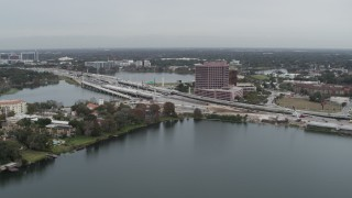 DX0003_233_026 - 5.7K stock footage aerial video of light freeway traffic and office building by a lake in Orlando, Florida
