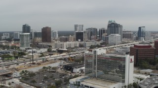 DX0003_233_031 - 5.7K stock footage aerial video fly away from city's skyline, reveal hotel, Downtown Orlando, Florida