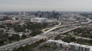 DX0003_234_001 - 5.7K stock footage aerial video of Amway Center, city skyline, and freeway interchange, Downtown Orlando, Florida