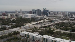DX0003_234_006 - 5.7K stock footage aerial video reverse view of Amway Center, city skyline, freeway interchange, Downtown Orlando, Florida