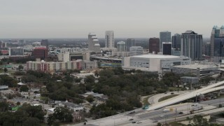 DX0003_234_023 - 5.7K stock footage aerial video slowly passing apartment complex, Amway Center and city skyline, Downtown Orlando, Florida