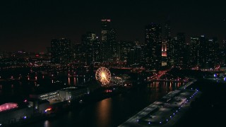 ED0001_000026 - HD stock footage aerial video of a reverse view of Navy Pier and Ferris wheel, and the skyline of Downtown Chicago at night, Illinois