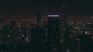 ED0001_000086 - HD stock footage aerial video of John Hancock Center skyscraper, with Willis Tower in the distance at night, Downtown Chicago, Illinois