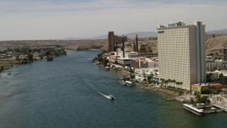 FG0001_000004 - 4K stock footage aerial video fly over a ferry on the Colorado River to pass riverfront hotels and casinos in Laughlin, Nevada