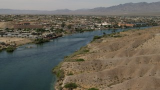 FG0001_000010 - 4K stock footage aerial video follow the Colorado River to approach riverfront homes and apartments in Bullhead City, Arizona