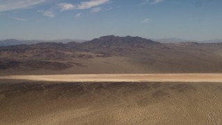 FG0001_000059 - 4K stock footage aerial video of a dry lake near Mojave Desert mountains in San Bernardino County, California