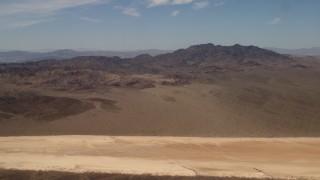 FG0001_000063 - 4K stock footage aerial video pan across Mojave Desert mountains near a dry lake in San Bernardino County, California