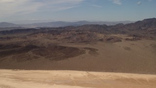 FG0001_000064 - 4K stock footage aerial video pan across Mojave Desert mountains, seen from a dry lake in San Bernardino County, California