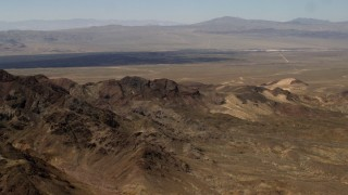 FG0001_000080 - 4K stock footage aerial video fly over rugged Mojave Desert mountains to approach Pisgah Crater in San Bernardino County, California