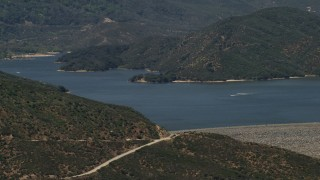 FG0001_000128 - 4K stock footage aerial video approach the lake and dam as speedboats cruise across Silverwood Lake, California
