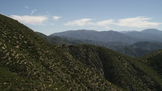 FG0001_000159 - 4K stock footage aerial video pan across and fly over steep green mountain slope in the San Gabriel Mountains, California