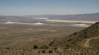 FG0001_000165 - 4K stock footage aerial video of towers and arrays of the Ivanpah Solar Electric Generating System, California, eclipsed by mountain