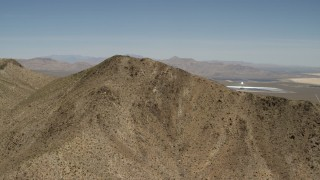 FG0001_000170 - 4K stock footage aerial video approach desert mountain near the Ivanpah Solar Electric Generating System in California