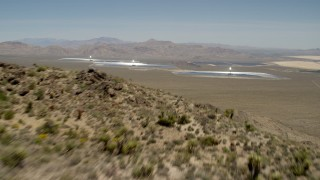 FG0001_000171 - 4K stock footage aerial video fly over a desert mountain to reveal the Ivanpah Solar Electric Generating System in California