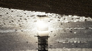 FG0001_000209 - 4K stock footage aerial video of a close-up view and orbit of a glowing power tower boiler at the Ivanpah Solar Electric Generating System in California