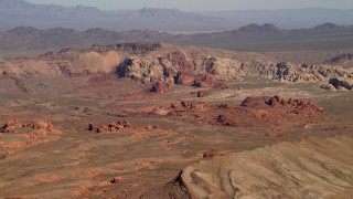 FG0001_000258 - 4K stock footage aerial video of red rock formations near a mountain ridge in the Nevada Desert