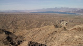 FG0001_000263 - 4K stock footage aerial video pan across desert hills and approach a scarred hill, with Lake Mead in the background, Nevada Desert