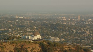 HDA06_08 - 1080 stock footage aerial video flyby Griffith Observatory overlooking the LA Basin at sunset, Hollywood Hills, California