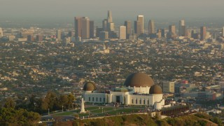 HDA06_09 - 1080 stock footage aerial video orbit the Griffith Observatory at sunset, and reveal the Downtown Los Angeles skyline, California