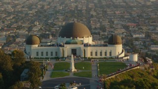 HDA06_10 - 1080 stock footage aerial video orbit the Griffith Observatory at sunset with tourists, California