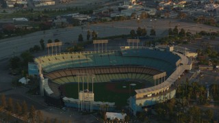 HDA06_18 - 1080 stock footage aerial video tilt from Dodger Stadium to reveal Los Angeles City Hall and Downtown Los Angeles at sunset