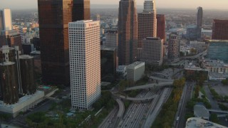 HDA06_44 - 1080 stock footage aerial video tilt from 110 freeway to reveal skyscrapers at sunset in Downtown Los Angeles, California