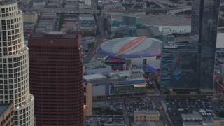 HDA06_64 - 1080 stock footage aerial video fly over skyscrapers to approach Staples Center and Nokia Theater at sunset, Downtown Los Angeles, California