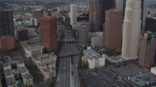 HDA06_67 - 1080 stock footage aerial video tilt from a bird's eye view of the 110 freeway to reveal skyscrapers in Downtown Los Angeles, California, twilight