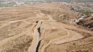 HDA07_19 - 1080 stock footage aerial video follow a road toward construction sites in Santa Clarita Valley, California