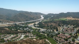 HDA07_26 - 1080 stock footage aerial video of fly over homes toward 14 freeway in Newhall, California