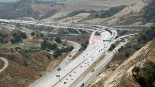 HDA07_29 - 1080 stock footage aerial video follow the 14 freeway to reveal the interchange at Newhall Pass, Santa Clarita, California