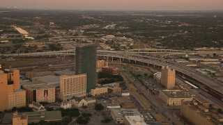 HDA12_013 - 1080 stock footage aerial video of flying away from freeway interchange to reveal skyscrapers at sunset in Downtown Fort Worth, Texas