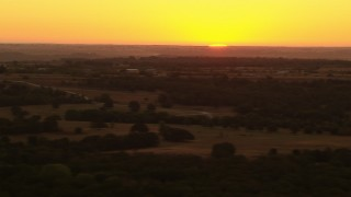 HDA12_038 - 1080 stock footage aerial video of the rising sun beyond farms and rural homes in Decatur, Texas