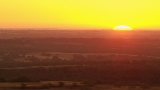HDA12_040 - 1080 stock footage aerial video pan from farmland to reveal rising sun in Decatur, Texas