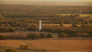 HDA12_067 - 1080 stock footage aerial video of flying by a silo on a farm at sunrise in Oklahoma
