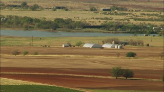 HDA12_100 - 1080 stock footage aerial video of farmland and barns by a lake in Temple, Oklahoma