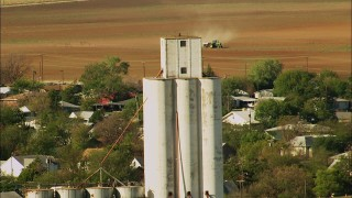 HDA12_102 - 1080 stock footage aerial video of silos and a tractor working a field in Temple, Oklahoma