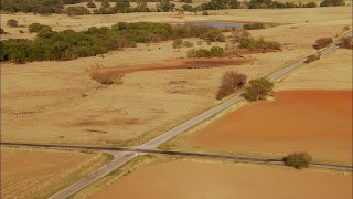 HDA12_121 - 1080 stock footage aerial video pass by country road and farmland with cows grazing near pond in Oklahoma