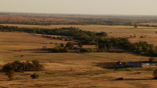 HDA12_129 - 1080 stock footage aerial video of a farmhouse and fields at sunset in Oklahoma