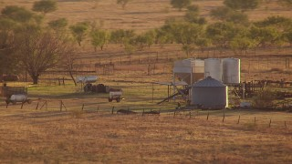 HDA12_137 - Aerial stock footage of 1080 aerial stock of silos and farm equipment at sunset in Oklahoma