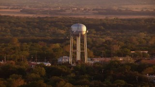 HDA12_150 - 1080 stock footage aerial video of flying by water tower, small businesses, Nocona, Texas, sunset