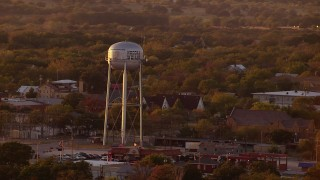 HDA12_151 - 1080 stock footage aerial video of a water tower and small town at sunset, Nocona, Texas