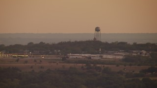 HDA12_171 - 1080 stock footage aerial video of a water tower at sunset in a small town, Decatur, Texas