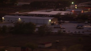 HDA12_179 - 1080 stock footage aerial video of a train running past an industrial building at night in Decatur, Texas