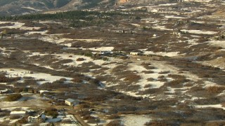 HDA13_284 - HD stock footage aerial video of flying over snowy fields and tilt to reveal homes and mountains, Castle Pines, Colorado