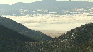 HDA13_305 - HD stock footage aerial video of Park Country valley with fog and snow on Rocky Mountains, Colorado