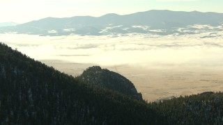 HDA13_306 - HD stock footage aerial video of a fog-shrouded valley and snowy Rocky Mountains, Park County, Colorado