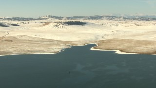 HDA13_312 - HD stock footage aerial video fly over a lake toward the opposite, snowy shore in Park County, Colorado