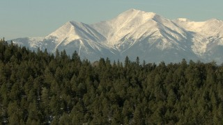 HDA13_322 - HD stock footage aerial video fly over trees-covered ridge to approach snowy Rocky Mountains, Colorado
