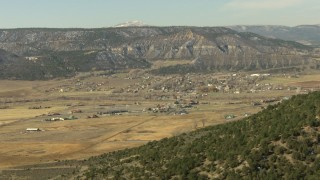 HDA13_345_03 - HD stock footage aerial video pan across a mountain ridge to reveal the small town of Ridgway, Colorado